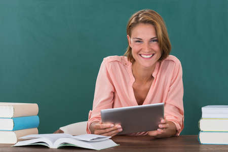 Young Happy Female Teacher With Books And Digital Tablet In Classroom