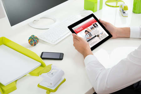 news online: Close-up Of Businessperson With Digital Tablet Showing Online News At Desk Stock Photo