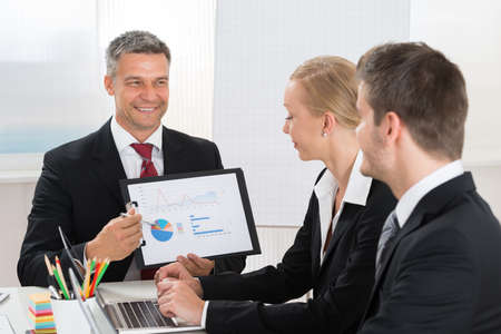 co workers: Mature Businessman Explaining Graph To His Co- Workers In Office Stock Photo