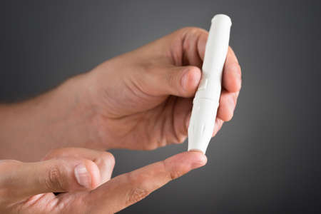 blood sugar level: Close-up Of Person Hands Checking Blood Sugar Level With Glucometer