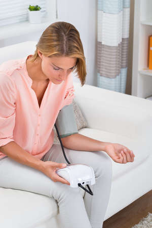 self exam: Young Woman Sitting On Sofa Checking Blood Pressure
