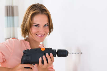 making hole: Portrait Of Young Woman Making Hole In Wall With Drill Machine Stock Photo