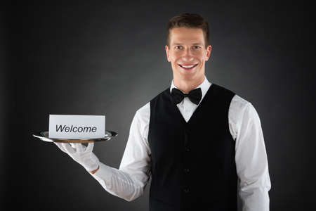 hospitality staff: Portrait Of Young Waiter Holding Plate With Welcome Text On Card Stock Photo