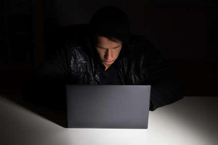 larceny: Male Hacker Stealing Data From Laptop In Office Stock Photo