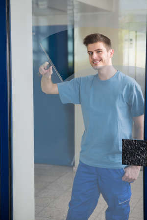 window cleaning: Young Male Worker Cleaning Glass With Squeegee