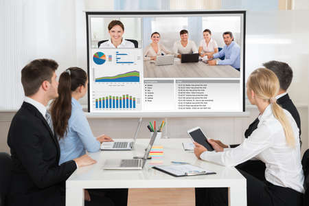 video conference: Group Of Businesspeople Attending Video Conference In Office