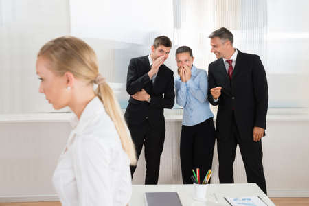 Group Of Happy Businesspeople Whispering About Woman In Office