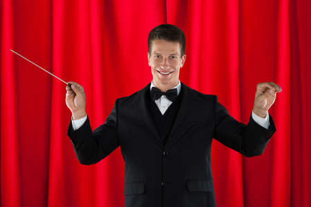 executive courses: Male Orchestra Conductor Holding Baton Over Red Curtain