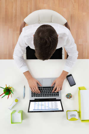gantt: High Angle View Of Businessman Working On Laptop Showing Gantt Chart At Desk Stock Photo