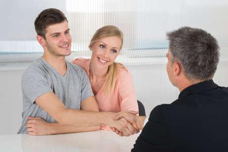 agente comercial: Pares jovenes felices que sacuden las manos con el Agente del varón en oficina Foto de archivo