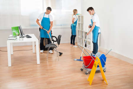 three shelves: Group Of Three Janitors In Blue Apron Cleaning Office Stock Photo