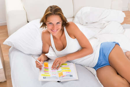 organizer page: Young Woman Writing In Diary While Lying In Bed