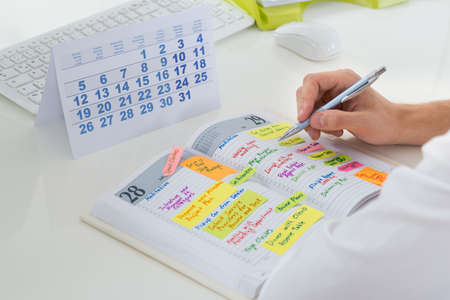 planner: Close-up Of Businessman With Calendar Writing Schedule In Diary