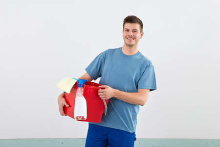 office cleanup: Young Happy Male Janitor With Bucket And Dispenser Bottle Stock Photo