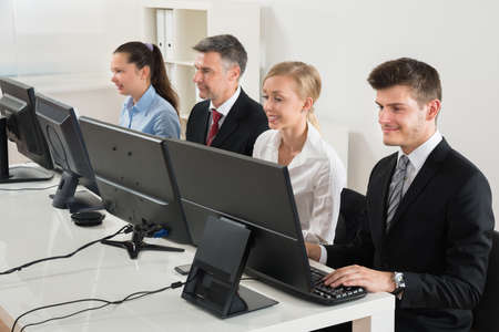 computer room: Group Of Businesspeople Typing On Desktop Computer At Desk Stock Photo