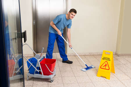 cleaning: Happy Male Janitor With Cleaning Equipments Mopping Floor