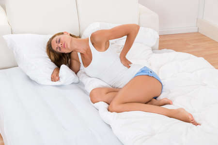 woman muscle: Young Woman Sitting On Bed Suffering From Back Pain
