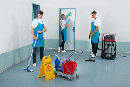 cleaning services: Group Of Janitors Cleaning Corridor With Cleaning Equipments