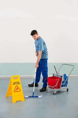 mopping: Young Male Worker With Cleaning Equipments Mopping Floor