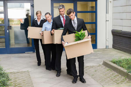 disappointed: Disappointed Businesspeople Standing In A Row With Cardboard Boxes Outside The Office Stock Photo