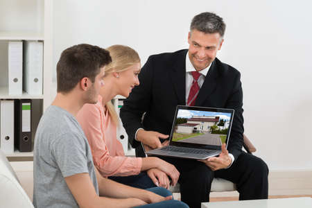 agents: Mature Estate Agent Showing House On Laptop To Young Couple