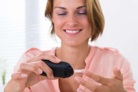 paciente: Primer De La Mujer Feliz Joven controla el nivel de glucosa con glucómetro