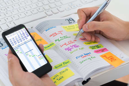 tasks: Close-up Of Person Hands With Mobile Phone And List Of Work In Diary Stock Photo
