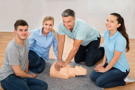 first class: Mature Male Instructor Showing Cpr Training On Dummy To His Student