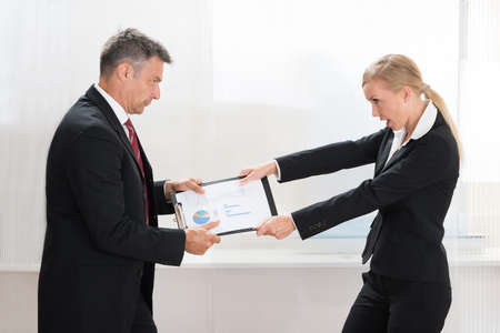 tugging: Portrait Of Two Businesspeople Pulling Clipboard With Graph Paper In Office Stock Photo