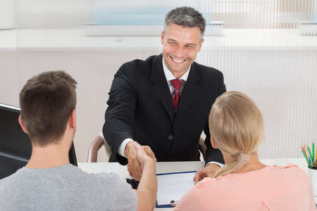 agente comercial: Agente masculino maduro que sacude las manos con el hombre en la oficina Foto de archivo
