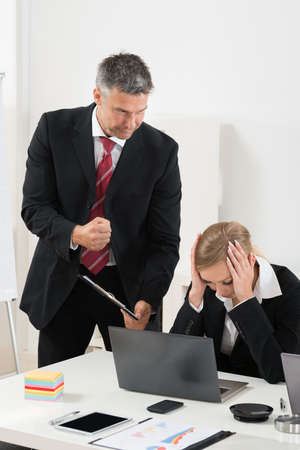 blaming: Boss With Clipboard Blaming To The Female Employee For Bad Results Stock Photo