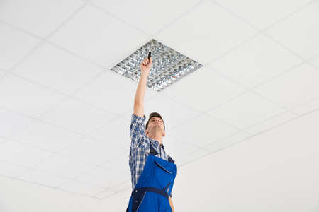 lighting technician: Male Electrician On Stepladder Installing Ceiling Light Stock Photo