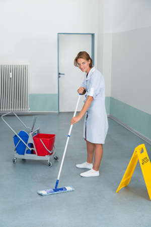 janitor: Young Female Janitor Mopping Floor With Wet Caution Sign And Cleaning Equipments