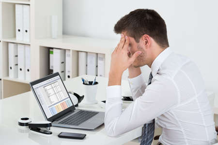 hoja de calculo: El hombre de negocios joven que se sienta con la computadora portátil en el escritorio que sufren de dolor de cabeza