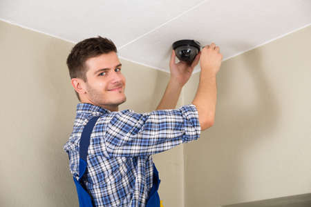 Young Male Technician Installing Surveillance Camera On Ceiling