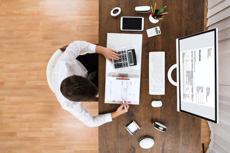 folders: High Angle View Of Young Male Accountant Checking Invoice In Office Stock Photo