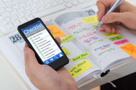 Close-up Of Person Hands Checking List From Mobile Phone And Diary