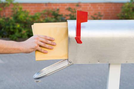 Close-up van de persoon die Putting Stapel brieven in de mailbox