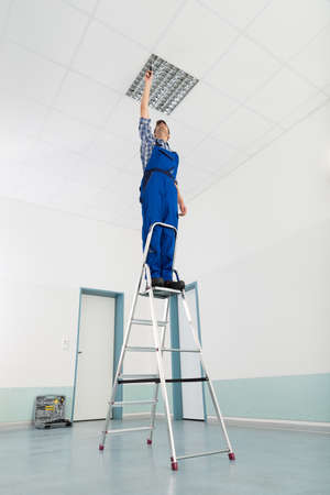 lightings: Male Electrician On Stepladder Installing Ceiling Light Stock Photo