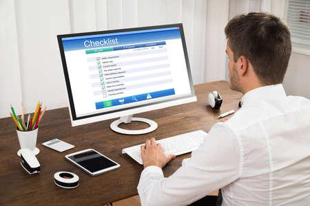 Young Businessman Filling Checklist Form On Computer At Wooden Desk Standard-Bild
