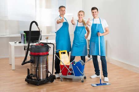 professionnel: Concierges heureux avec aspirateur et équipements de nettoyage en Bureau Banque d'images