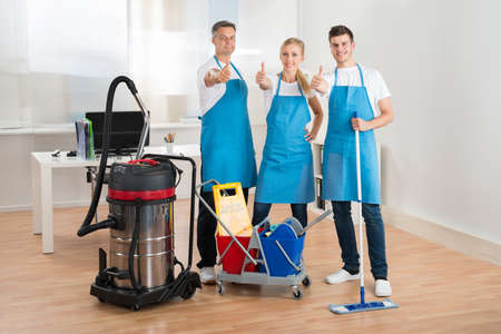 Gl�ckliche Hausmeister mit Staubsauger und Putzmittel Im B�ro Lizenzfreie Bilder