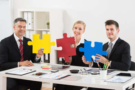 jigsaw puzzle pieces: Team Of Happy Businesspeople Holding Multi-colored Jigsaw Puzzle In Office