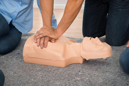 reanimate: Close-up Of Person Practicing Cpr Chest Compression On Dummy