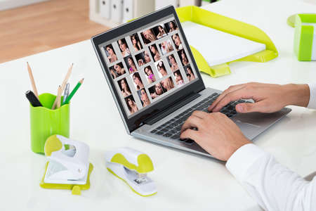 retouch: Close-up Of Businessperson Working With Photographs On Laptop At Desk