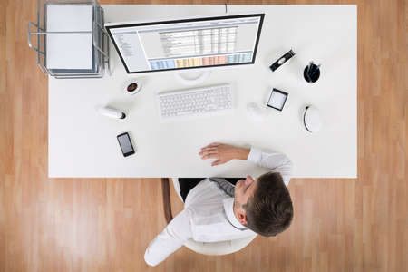 spreadsheets: High Angle View Of Young Businessman Suffering From Backache In Office Stock Photo
