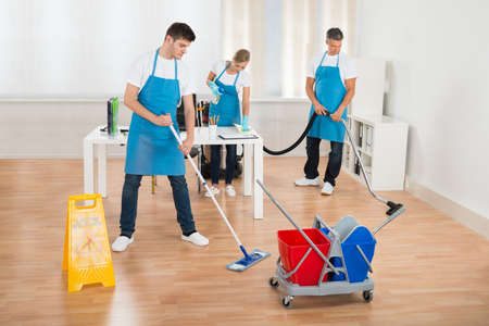Cleaners Team In Uniform Cleaning Wooden Floor In Office