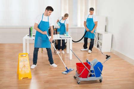 mujer limpiando: Limpiadores Equipo En Uniforme limpieza de suelos de madera en la oficina