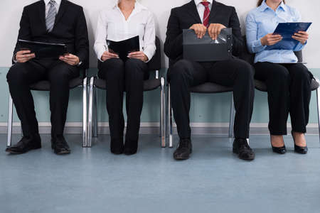 line of people: Close-up Of Businesspeople With Files Sitting On Chair
