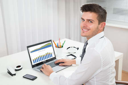 young businessman: Young Happy Businessman Working With Graph On Laptop In Office Stock Photo